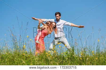Family doing the plane on summer meadow under clear blue sky