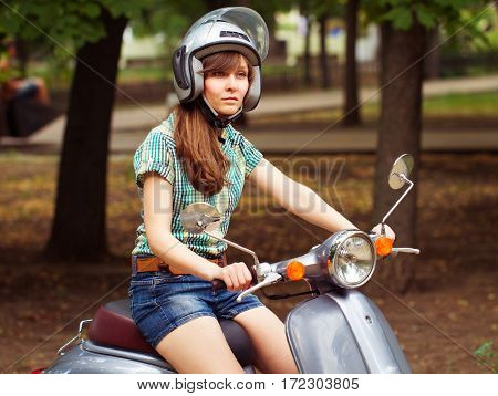 Young Woman On Scooter Rear View In A City Park. Close Up