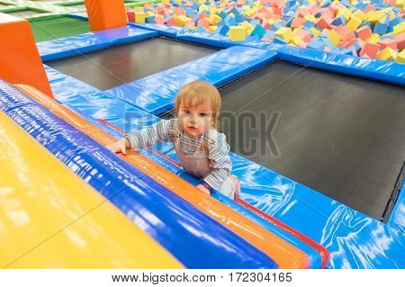 The One Year Old Baby Cute Playing In Indoors Playground.