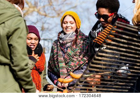 Multi-ethnic group of five young people having fun at barbecue
