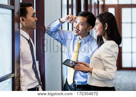 Indonesian co-workers, men and woman, in office hallway talk about business project