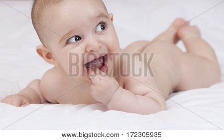 Beautiful cute teething baby biting fingers with funny expression on white background.