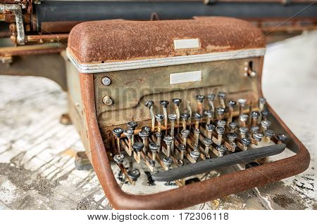 Old rusted typewriter on the wooden surface. Closeup low aperture photo. Horizontal.