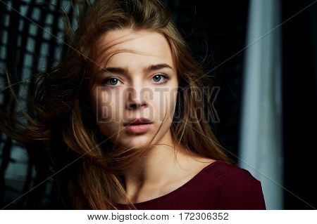 Beautiful girl looks piercing eyes into the camera. Hair flying. Drama. Studio photography in low key on a background
