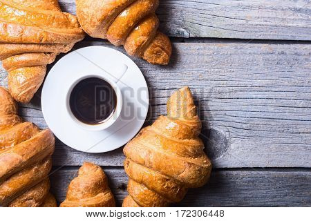 Tasty buttery croissants and coffee on old wooden table .