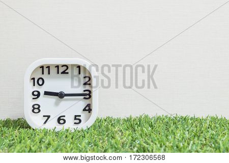 Closeup white clock for decorate show a quarter past nine or 9:15 a.m. on green artificial grass floor and cream wallpaper textured background with copy space