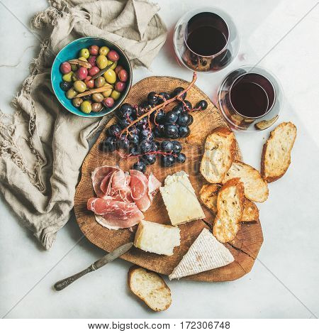 Wine and snack set. Variety of cheese, olives in blue bowl, prosciutto, roasted baguette slices, grapes on wooden board and glasses of red wine over grey marble background, top view, square crop
