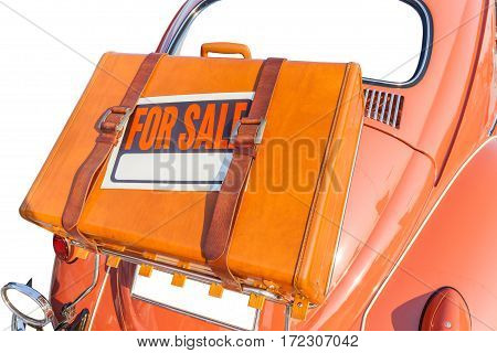 For sale sign stick on brown traveling leather bag carry behind the brown retro car on white background exclusive and retro automobile trading.