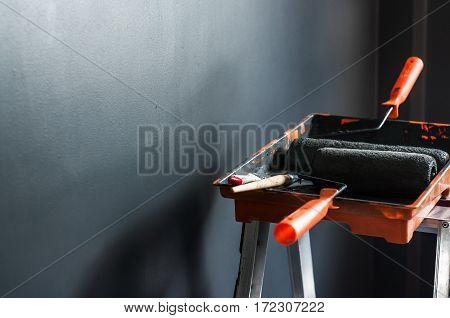 Set of paint tools paint brushes paint roller in paint tray for painting Grey wall background Copy space.