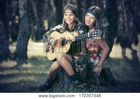 Two happy teen girls with guitar in a summer forest. Stylish fashion model outdoor