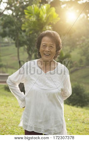 Portrait of healthy happy Asian senior woman enjoying morning workout at outdoor nature park, beautiful sunlight background.