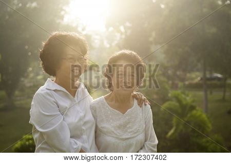 Portrait of healthy Asian seniors mother and daughter enjoying life at outdoor nature park, morning beautiful sunlight background.