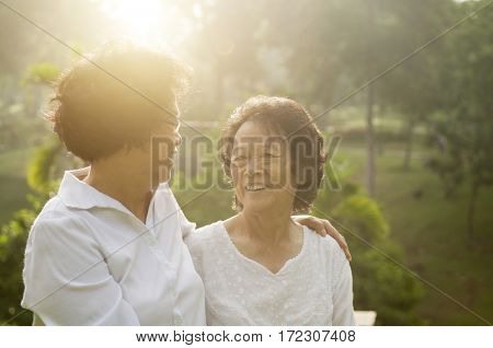 Portrait of healthy Asian seniors mother and daughter having fun at outdoor nature park, morning beautiful sunlight background.