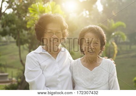 Portrait of healthy Asian seniors mother and daughter relaxing at outdoor nature park, morning beautiful sunlight background.
