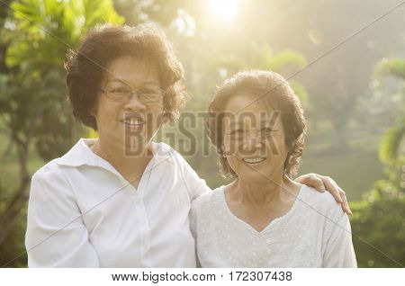Portrait of healthy Asian seniors mother and daughter smiling at outdoor nature park, morning beautiful sunlight background.