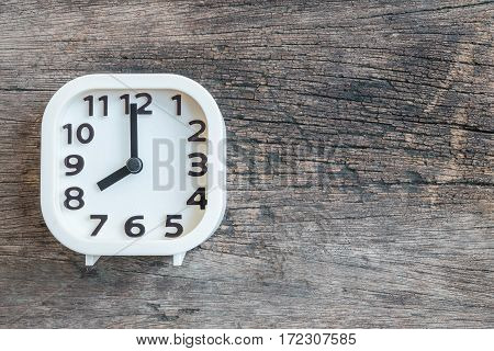 Closeup white clock for decorate in 8 o'clock on old wood floor textured background with copy space