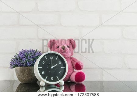 Closeup black and white alarm clock for decorate in 2 o'clock with bear doll and plant on black glass table and white brick wall textured background with copy space