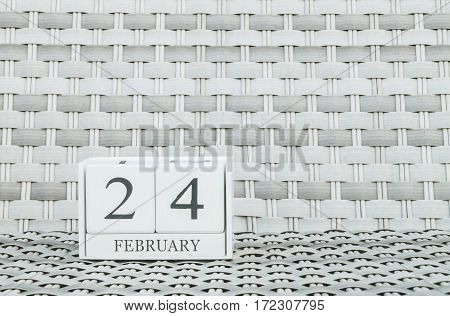 Closeup surface white wooden calendar with black 24 february word on blurred weave wood chair textured background with copy space in selective focus at the calendar