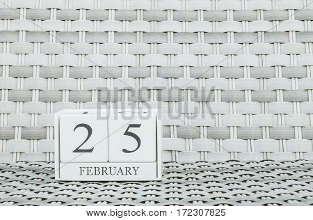 Closeup surface white wooden calendar with black 25 february word on blurred weave wood chair textured background with copy space in selective focus at the calendar