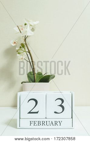 Closeup white wooden calendar with black 23 february word with white orchid flower on white wood desk and cream color wallpaper in room textured background in selective focus at the calendar