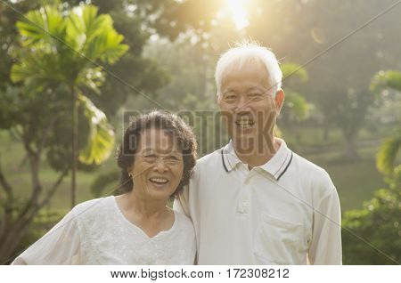 Portrait of healthy and happy Asian seniors retiree couple having activities at outdoor nature park, morning beautiful sunlight background.