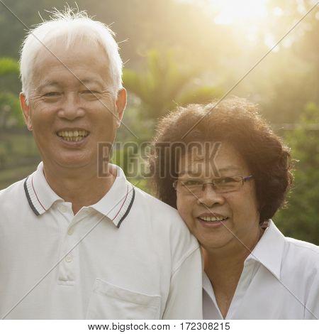 Portrait of healthy Asian seniors retiree couple enjoying life at outdoor nature park, morning beautiful sunlight background.