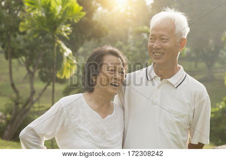 Portrait of healthy and happy Asian seniors retiree couple having fun at outdoor nature park, morning beautiful sunlight background.
