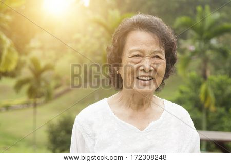 Portrait of healthy happy Asian senior woman smiling at outdoor nature park, morning beautiful sunlight background.