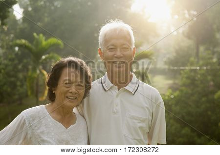 Portrait of healthy Asian seniors retiree couple having activities at outdoor nature park, morning beautiful sunlight background.
