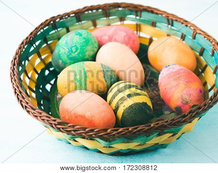 Funny Colorful Easter eggs hand painted by kids in basket on green pastel background
