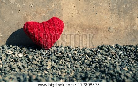 Valentine's concept. Red heart on dark grey gravel texture background with copy space. Vintage and retro color.