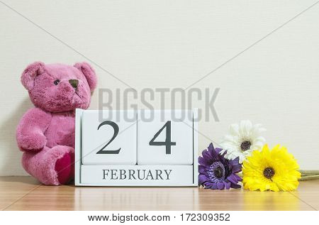 Closeup surface white wooden calendar with black 24 february word on brown wood desk and cream color wallpaper in room textured background with copy space in selective focus at the calendar