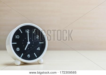 Closeup alarm clock for decorate in 7 o'clock on brown wood desk and wall textured background with copy space