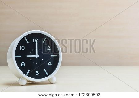 Closeup alarm clock for decorate in 9 o'clock on brown wood desk and wall textured background with copy space