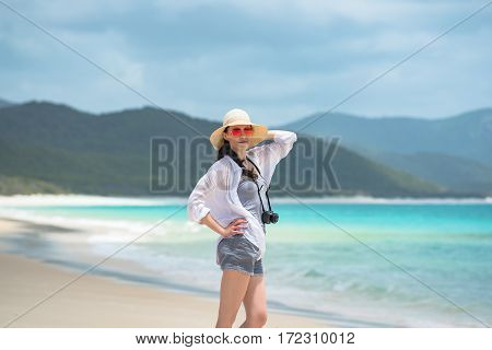 Young woman tourist with photo camera on the beach. Whitehaven beach Whitsunday island Australia
