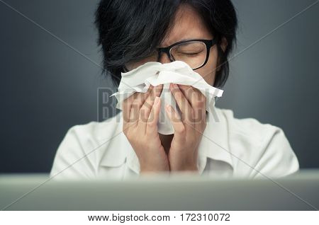 Close up of sad woman with a tissue. Short hair female sneezing. ILLness depression and allergy concept. Asian woman wear eyeglasses sneezing in a tissue. laptop foreground.