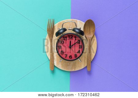 Meal time with alarm clock at lunch time, top view