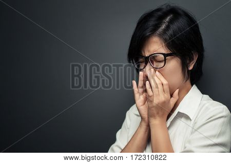 Asian short hair woman sneezing. ILLness depression and allergy concept. Asian woman wear eyeglasses with sinus pain.