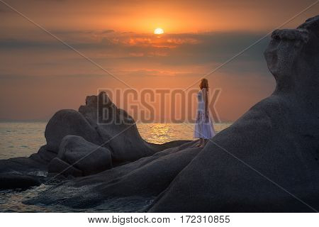 Beautiful girl on the rocky beach watching idyllic sunset by the sea.