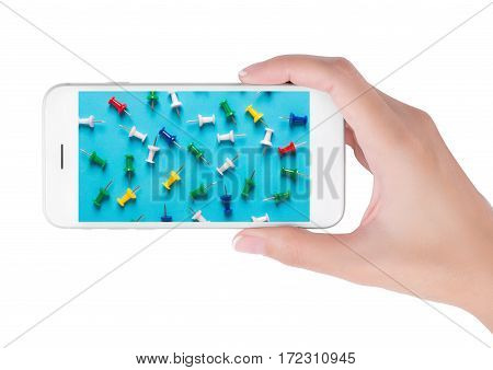 Woman using smart phone searching colorful collection of push pins in grouping on blue background. Object and Office supplies concept isolated on white background.