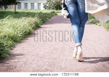 Girl In Jeans Walking Along The Path Of The Camera, Rear View, High Heel Shoes