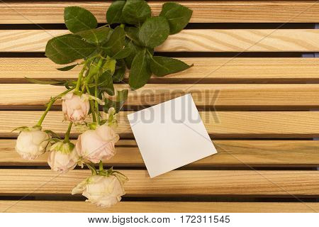 Pink rose bouquet closup sticker note on a wooden bench background