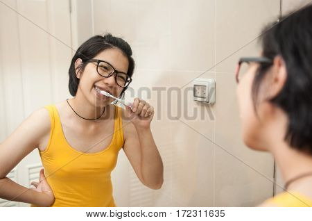 Portrait of Asian glasses woman brushing the teeth in bathroom. Happiness of beautiful girl in yellow undershirt smiling and looking through mirror.