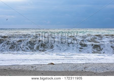 Sea colors with waves after a storm on cloudy sky.