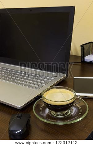 Comfortable working place in office with mousetelephone and cup of coffee on desk