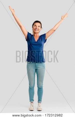 Portrait of a happy middle aged brunette with arms up