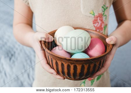 Close-up partial view of little girl holding bowl with colorful Easter eggs