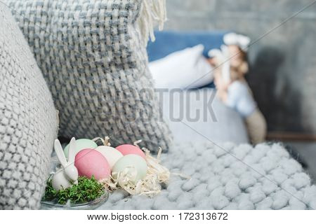 Beautiful composition of decorative bunny and painted easter eggs on shavings