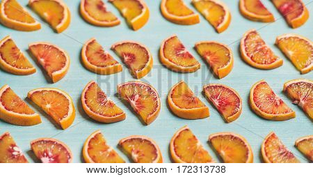 Natural fruit pattern concept. Fresh juicy blood orange slices placed in rows over light blue painted table background, selective focus