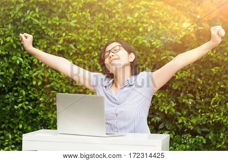 Asian business woman enjoying with her work on grass background. Outstretched arms fresh morning air with sunlight. Green nature office. Happiness glasses girl relaxing and deep breathing fresh air.